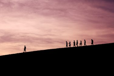 a group of people following one person