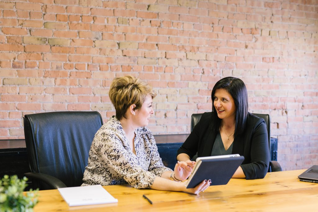 two woman in the office talking to each other